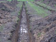 green energy_heat_pump_ground_loops_being_laid_in_trenches